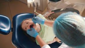 招待会的女孩牙医的, stomatologist审查儿童` s牙,逗人喜爱和淘气女孩微笑 股票视频