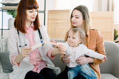 招待会的母亲和小小孩儿童儿科医生的 女性小的不适的儿科医生审查的喉头 免版税库存图片