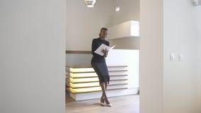 招待会的Elegent美国黑人的夫人有自然构成和迷人的微笑的是读和填装在 库存图片