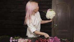 招标的正面图,安排花的白色衬衣的女孩由在花束的花 户内 股票视频