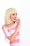 读招贴的微笑的白肤金发的女孩 库存照片