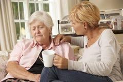 拜访不快乐的资深母亲的成人女儿在家坐沙发 免版税库存图片