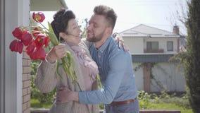 拜访他的祖母的成人孙子,带来郁金香她的花束  拥抱他的老婆婆的有胡子的人 ?? 股票录像