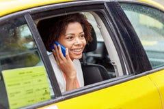 拜访在出租汽车的愉快的非洲妇女智能手机 免版税库存照片