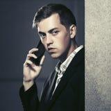 拜访在城市街道的年轻英俊的商人手机 库存图片