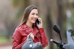 拜访在摩托车的愉快的motorbiker电话 库存照片