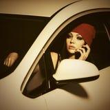 拜访手机的年轻时尚妇女驾驶汽车 免版税库存照片