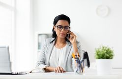 拜访智能手机的女实业家在办公室 免版税图库摄影