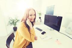 拜访智能手机的女实业家在办公室 免版税库存图片