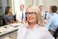 拜访智能手机的微笑的女实业家 免版税库存图片