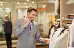 拜访智能手机的愉快的人在服装店 免版税库存图片