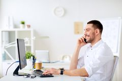 拜访智能手机的愉快的商人在办公室 库存图片