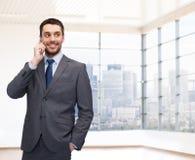 拜访智能手机的愉快的年轻商人 免版税库存图片