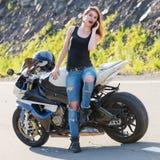 拜访电话的女孩在摩托车附近 库存图片