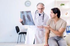 拜访老男性医生放射学家的年轻人 免版税图库摄影