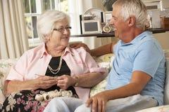 拜访资深母亲的成人儿子在家坐做钩针编织的沙发 免版税库存照片