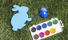 拟订与标志的兔宝宝对此` s手,绘鸡蛋入蓝色 库存照片