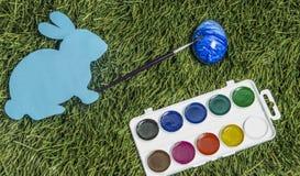 拟订与油漆刷的兔宝宝对此` s手,绘鸡蛋入蓝色 库存照片