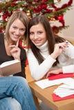 拟订圣诞节写年轻人的二名妇女 免版税库存照片