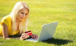 拟订dof重点现有量在线浅购物非常 有膝上型计算机的微笑的白肤金发的女孩 免版税库存图片
