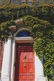 围拢一个大厦的红色门绿色常春藤在都伯林市 库存图片