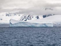 围拢多山海岸线的低云和冰山 免版税库存图片