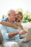 拥抱一个人的微笑的资深妇女在客厅,当使用膝上型计算机时 免版税库存照片