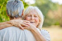 拥抱一个人的微笑的资深妇女 库存图片