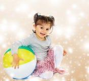 拥抱一个大球的小女孩 库存照片