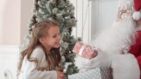 拥抱一个小逗人喜爱的女孩和给她的圣诞节礼物的圣诞老人 免版税库存照片