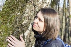 拥抱一个巨大的树干的女孩在公园,微笑对照相机 自然的保护的概念 库存照片
