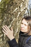 拥抱一个巨大的树干的女孩在公园,微笑对照相机 自然的保护的概念 免版税库存图片