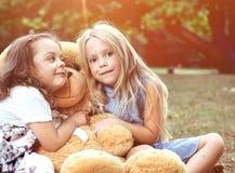 拥抱一个巨大的玩具熊的两个逗人喜爱的女孩 库存照片