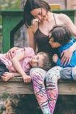 拥抱一个木房子的大阳台的妇女孩子 库存照片