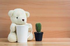 拥抱一个杯子和仙人掌在棕色木背景的白熊 库存图片