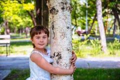 拥抱一个桦树的女孩在公园 免版税库存照片