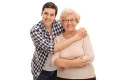 拥抱一个资深夫人的年轻人 免版税库存图片