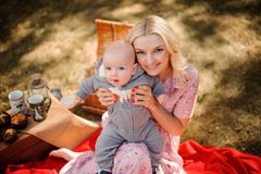 拥抱一个逗人喜爱的小儿子的白肤金发的母亲 免版税图库摄影