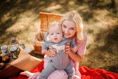 拥抱一个逗人喜爱的小儿子的美丽的白肤金发的母亲 免版税库存图片