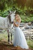 拥抱一匹灰色马, outd的礼服的美丽的苗条白肤金发的女孩 库存图片