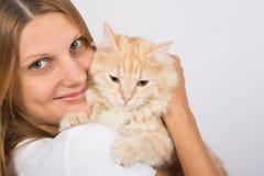 拥抱一只不悦的猫的女孩 库存照片