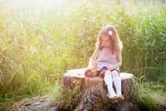 拥抱一只兔子的三岁的卷发的欧洲女孩在夏天公园 免版税图库摄影