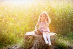 拥抱一只兔子的三岁的卷发的欧洲女孩在夏天公园 库存图片