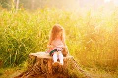 拥抱一只兔子的三岁的卷发的欧洲女孩在夏天公园 免版税库存照片