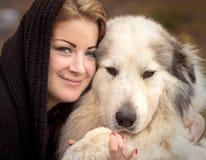 拥抱一只大牧羊犬的妇女 免版税库存照片