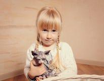 拥抱一只小sphynx小猫的逗人喜爱的小女孩 免版税库存图片