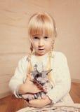 拥抱一只小sphynx小猫的逗人喜爱的小女孩 免版税库存照片