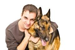 拥抱一只德国牧羊犬的人 库存图片