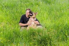 拥抱一只德国牧羊犬的人 图库摄影