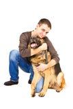 拥抱一只德国牧羊犬的愉快的年轻人 图库摄影